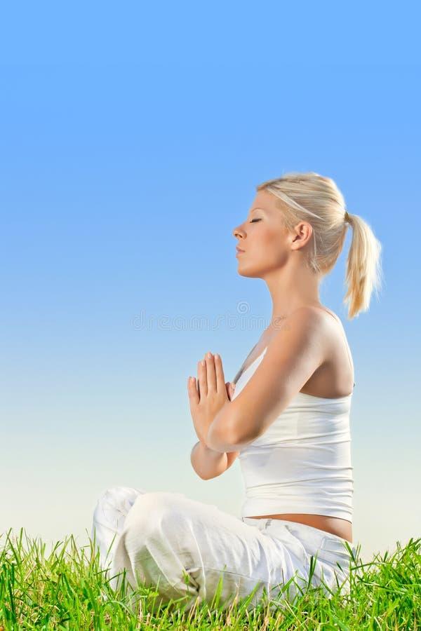 Donna che fa esercitazione di meditazione di yoga immagine stock