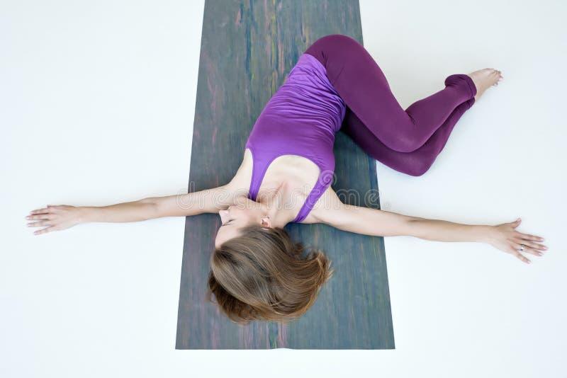 Donna che fa esercizio di yoga su variazione del pavimento della posa di torsione della pancia fotografie stock libere da diritti