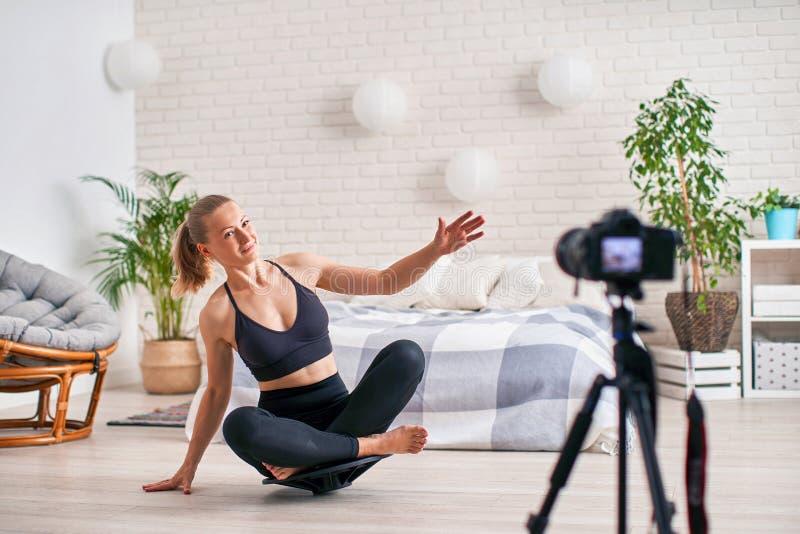 Donna che fa esercizio su un compensatore speciale del simulatore gli abiti sportivi atletici biondi, casa si sono esercitati rin fotografia stock