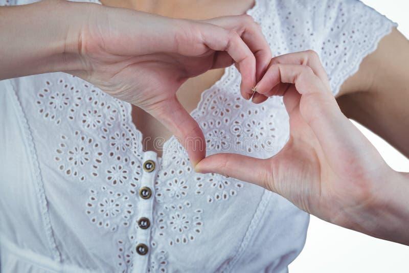 Donna che fa forma del cuore con le mani immagini stock