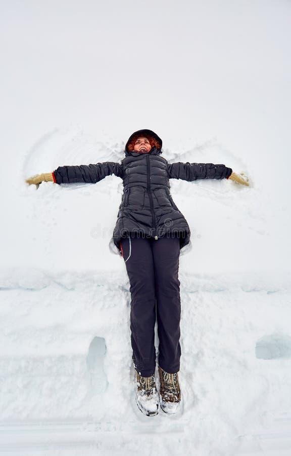 Donna che fa gli angeli della neve fotografia stock