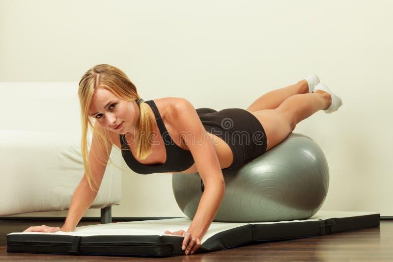 Donna che fa gli esercizi di forma fisica con la palla di misura immagine stock