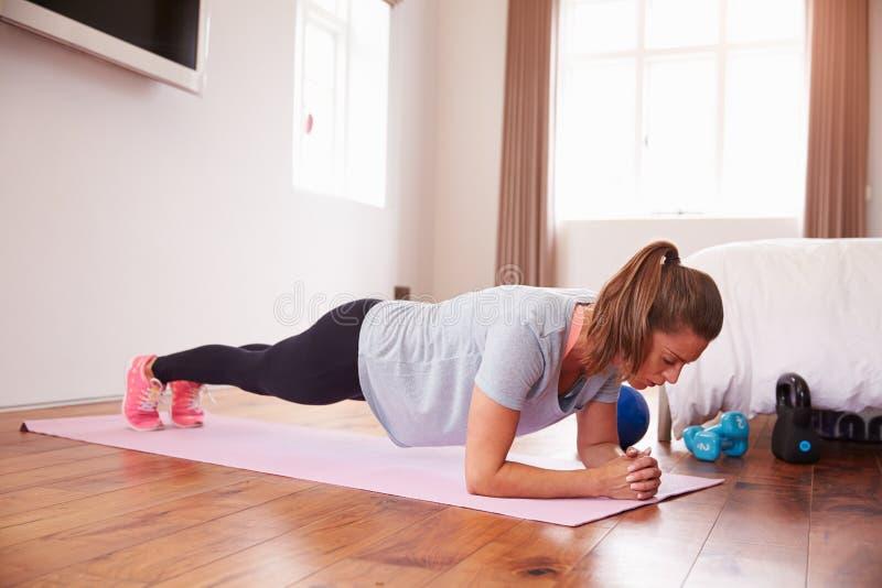 Donna che fa gli esercizi di forma fisica su Mat In Bedroom fotografia stock libera da diritti
