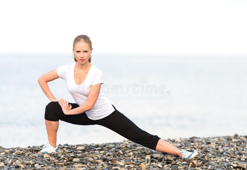 Donna che fa gli esercizi di sport e di yoga sulla spiaggia fotografia stock