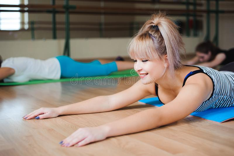 Donna che fa gli esercizi in palestra, addestramento di yoga della ragazza di forma fisica di sport che allunga studio fotografie stock