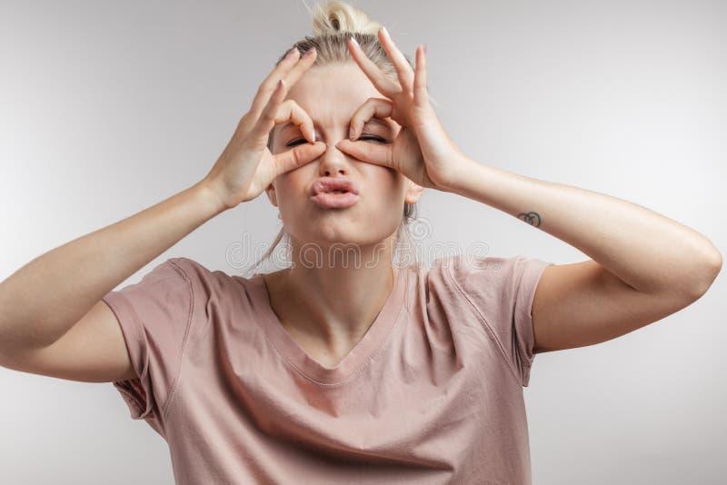 Donna che fa i cerchi facendo uso delle sue mani intorno ai suoi occhi e che sorride alla macchina fotografica immagine stock
