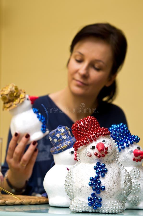 Donna che fa il pupazzo di neve del giocattolo fotografia stock