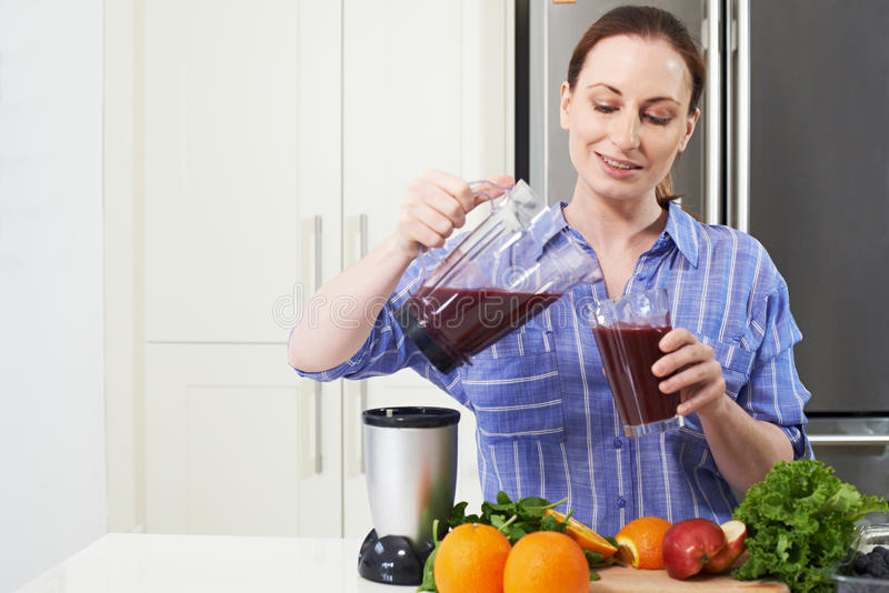 Donna che fa Juice Or Smoothie In Kitchen fotografie stock