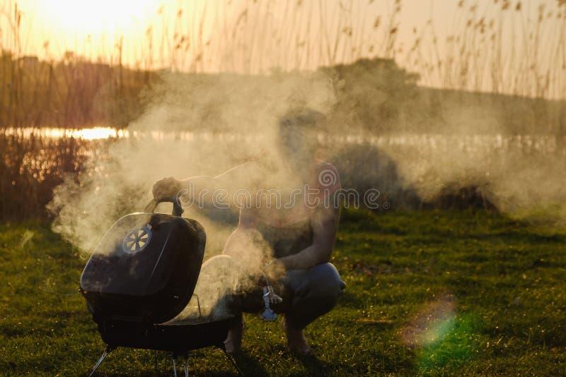 Donna che fa kebab del bbq sulla griglia con carne e le verdure Tramonto di estate sulla sponda del fiume immagini stock libere da diritti