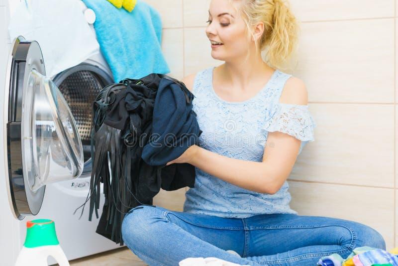 Donna che fa la lavanderia nera dei vestiti fotografia stock