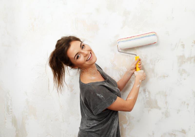 Donna che fa la pittura della parete immagini stock libere da diritti