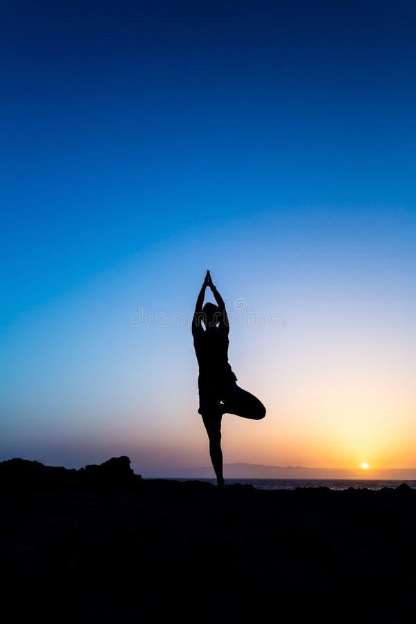 Donna che fa la siluetta di tramonto di yoga fotografia stock libera da diritti