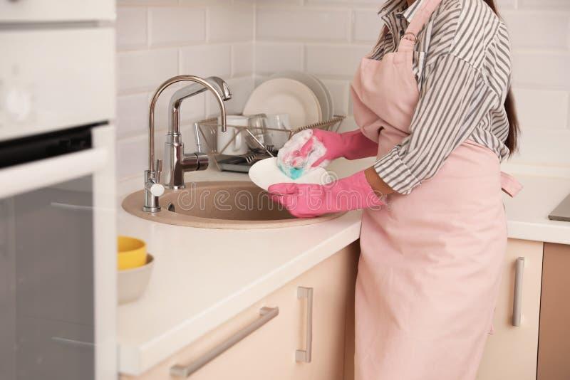 Donna che fa lavaggio su nel lavandino di cucina, vista del primo piano immagini stock libere da diritti
