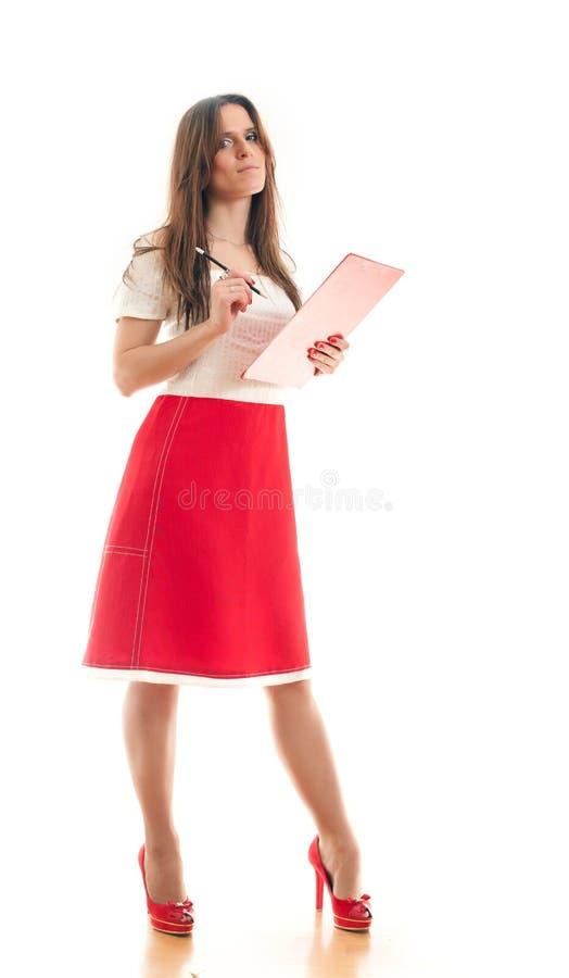 Donna che fa le note nel suo raccoglitore immagine stock