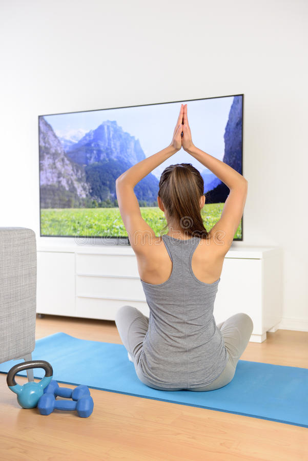 Donna che fa meditazione domestica di yoga davanti alla TV immagini stock