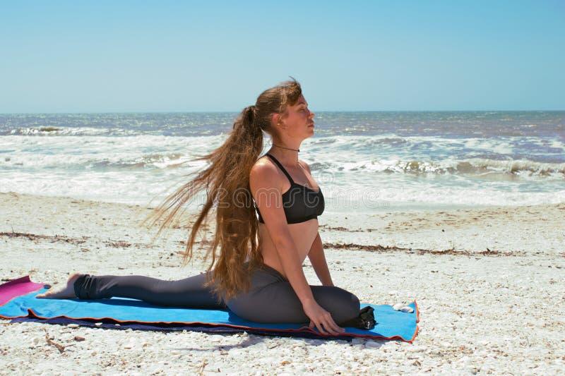Donna che fa posa del piccione di yoga sulla spiaggia fotografia stock