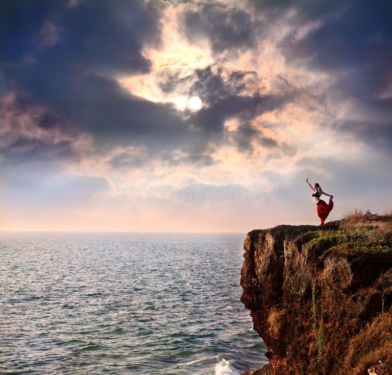 Donna che fa posa di yoga del danzatore di natarajasana immagini stock