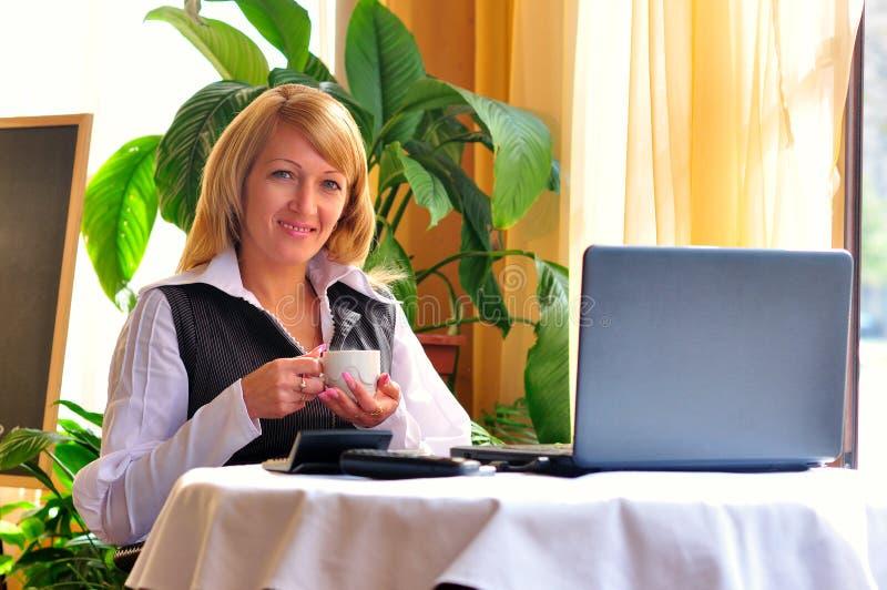 Donna che fa qualcosa in computer portatile fotografie stock libere da diritti