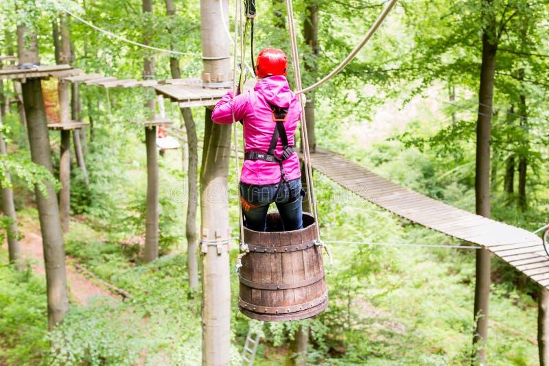 Donna che fa scorrere nel barilotto al corso rampicante dell'alta corda fotografia stock