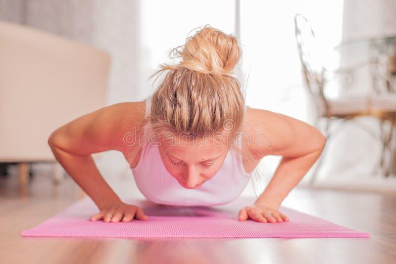Donna che fa spinta-UPS sulla stuoia di yoga a casa Ragazza di forma fisica che fa i piegamenti sulle braccia sulla stuoia di ese fotografia stock