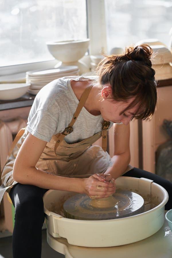 Donna che fa terraglie ceramiche sulla ruota, luce del sole Concetto per la donna lavoratrice in indipendente, affare, hobby fotografie stock