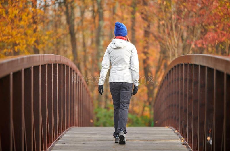 Donna che fa un'escursione al giorno di autunno immagine stock libera da diritti