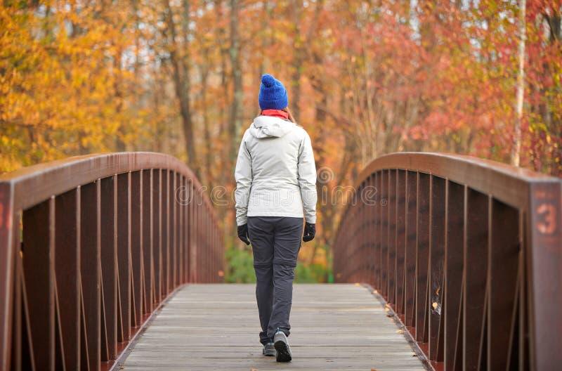 Donna che fa un'escursione al giorno di autunno fotografia stock libera da diritti