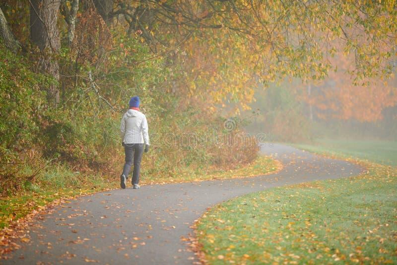 Donna che fa un'escursione al giorno nebbioso di autunno immagine stock libera da diritti