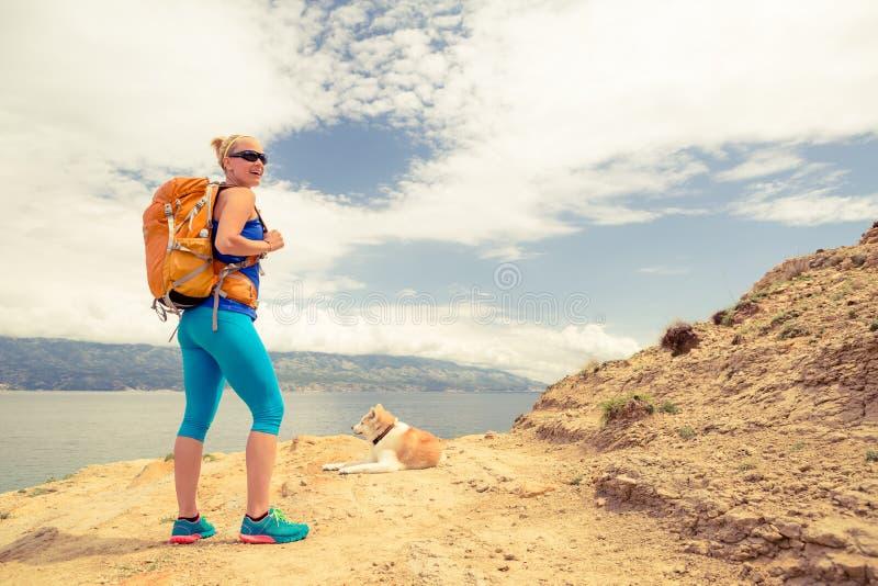 Donna che fa un'escursione camminata con il cane sul paesaggio del mare immagini stock libere da diritti