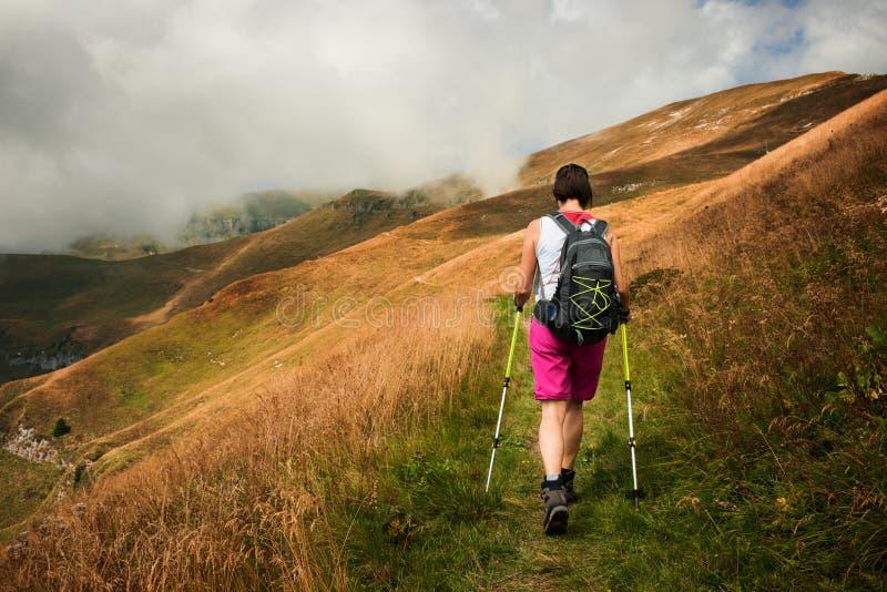 Donna che fa un'escursione facendo uso dell'escursione dei pali fotografie stock