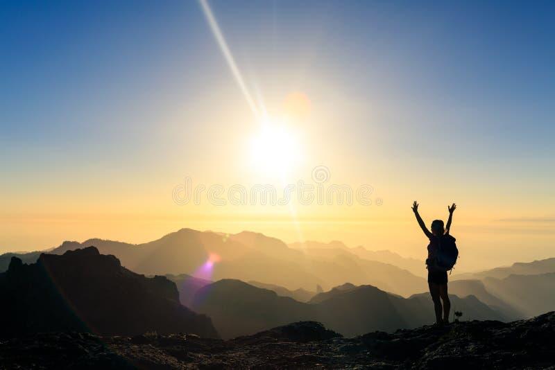 Donna che fa un'escursione la siluetta di successo nel tramonto delle montagne fotografia stock