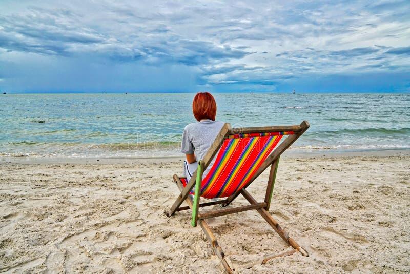 Donna che fa un picnic e che trascura il mare che si siede su una sedia rossa alla spiaggia fotografie stock