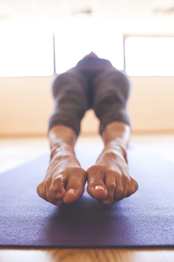 Donna che fa yoga al pavimento di legno fotografia stock libera da diritti
