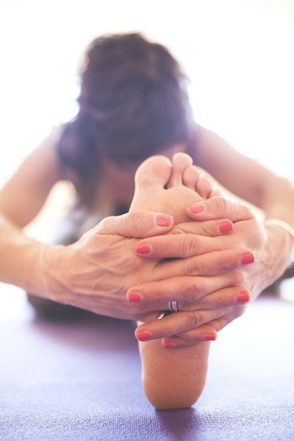 Donna che fa yoga al pavimento di legno immagini stock
