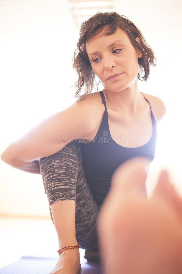 Donna che fa yoga al pavimento di legno immagine stock libera da diritti