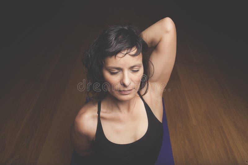 Donna che fa yoga al pavimento di legno fotografia stock