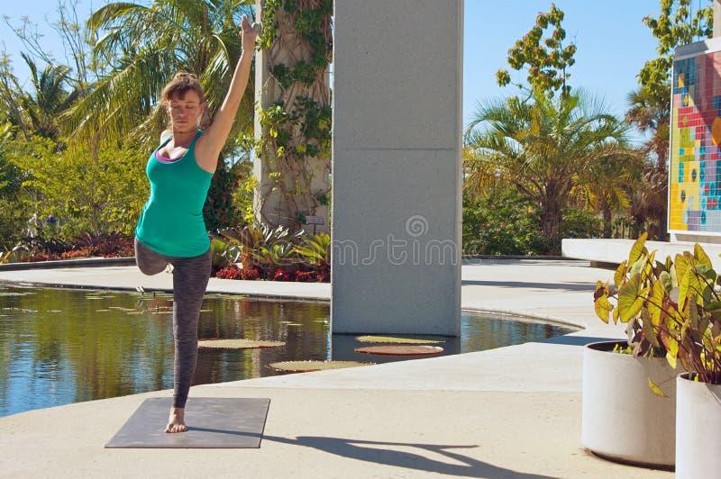 Donna che fa yoga all'aperto nella posa del danzatore fotografia stock