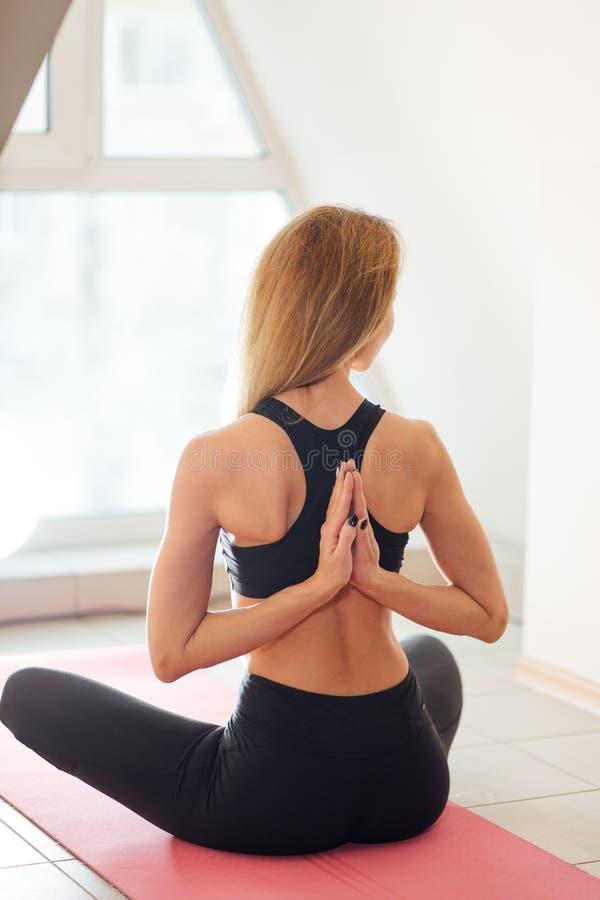 Donna che fa yoga nella posa inversa di preghiera Pashchima Namaskarasana fotografia stock