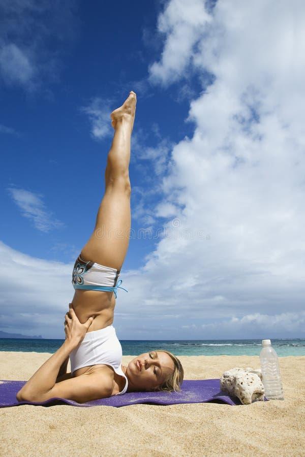 Donna che fa yoga sulla spiaggia. fotografia stock