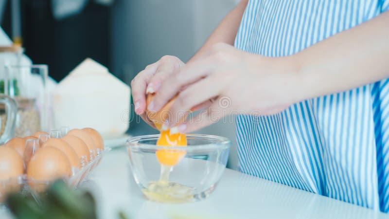 Donna che fende un uovo in una ciotola con fare una pausa nella cucina fotografia stock libera da diritti