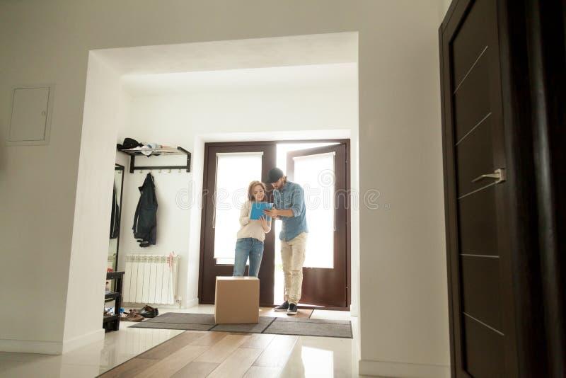 Donna che firma per il pacchetto che riceve scatola dal corriere a casa fotografie stock
