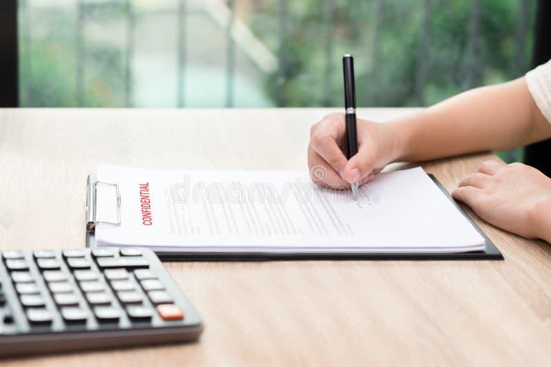 Donna che firma sul contratto confidenziale con il calcolatore su di legno fotografia stock libera da diritti