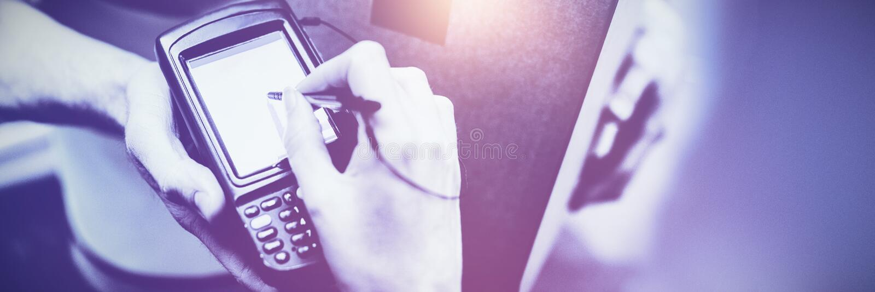 Donna che firma sul dispositivo al pacchetto di consegna fotografia stock