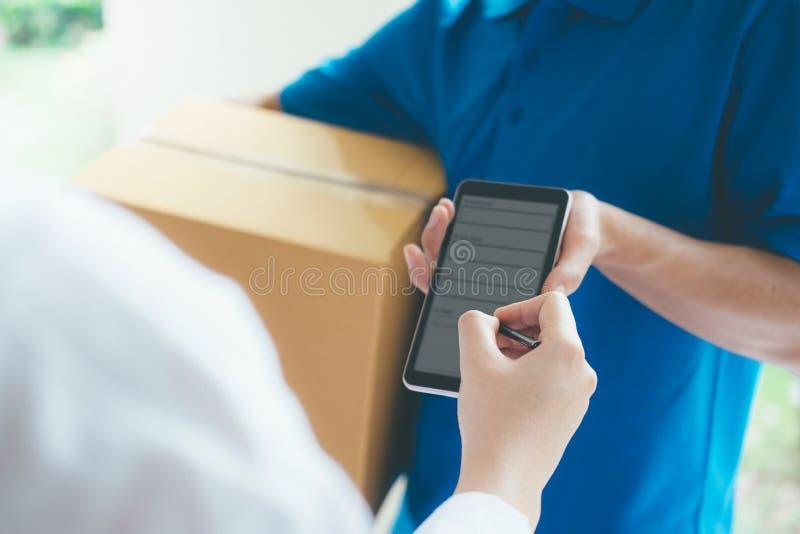 Donna che firma sul dispositivo digitale al pacchetto di consegna fotografia stock