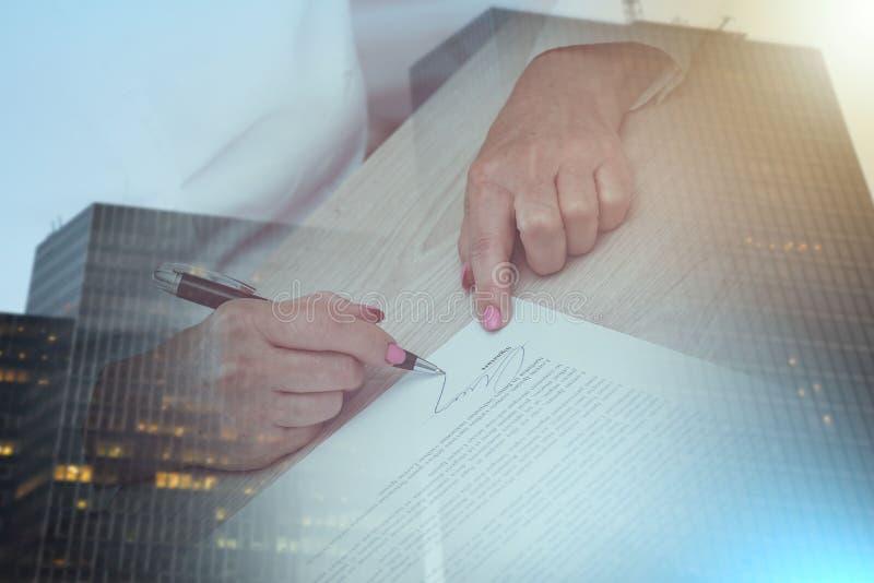Donna che firma un contratto; esposizione multipla fotografie stock libere da diritti