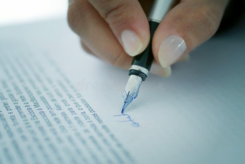 Donna che firma un documento fotografia stock