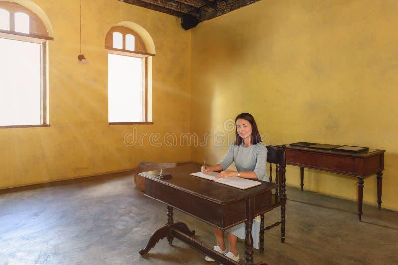 Donna che firma un libro di ospite con una penna fotografia stock