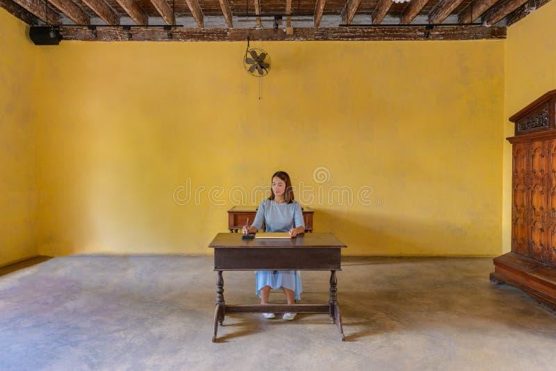 Donna che firma un libro di ospite con una penna immagine stock