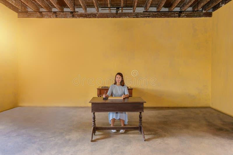 Donna che firma un libro di ospite con una penna immagini stock