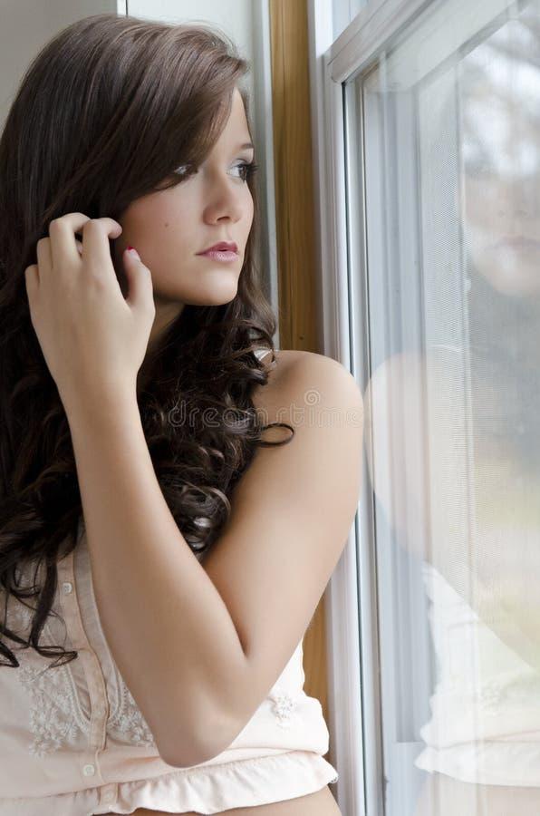 Donna che fissa alla finestra fotografie stock